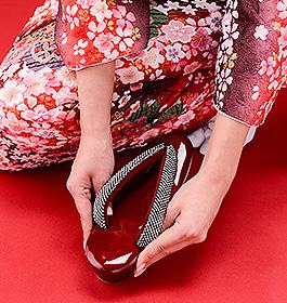 草履を調節する。足指に引っ掛ける感じで履く。